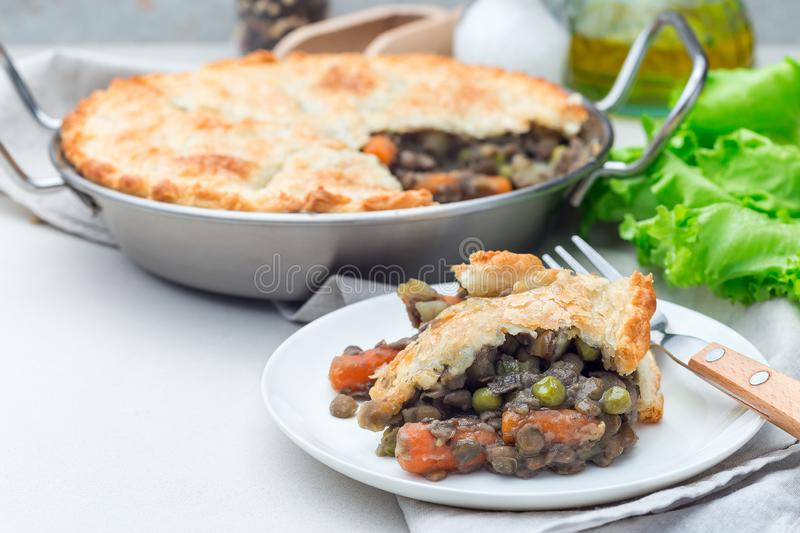 Vegetarian pot pie with lentil, mushrooms, potato, carrot and green peas, covered with puff pastry, on white plate, horizontal, royalty free stock photos