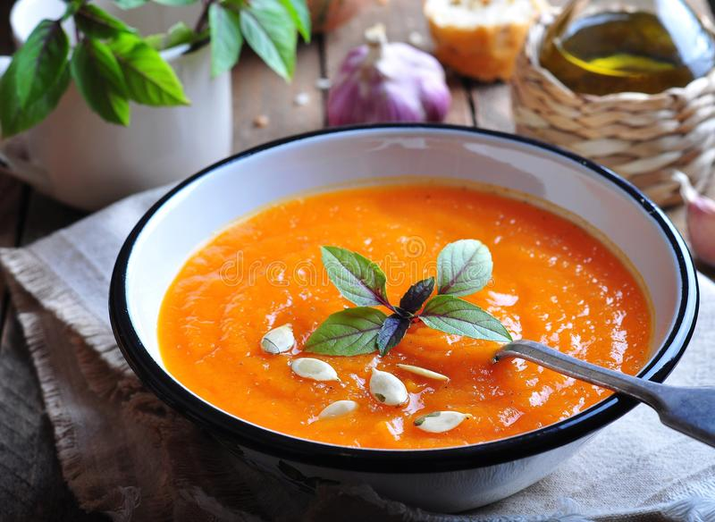 Vegetarian pumpkin soup with garlic, basil and olive oil stock photo