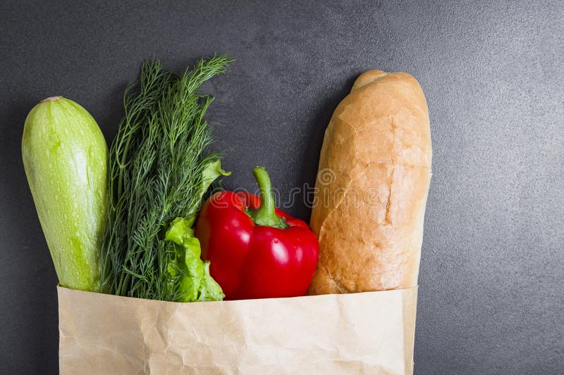 Vegetarian purchases at grocery store. Vegetables in paper bag on black background. Healthy food concept. Pack with vegetables. Zucchini, dill, greens stock photo