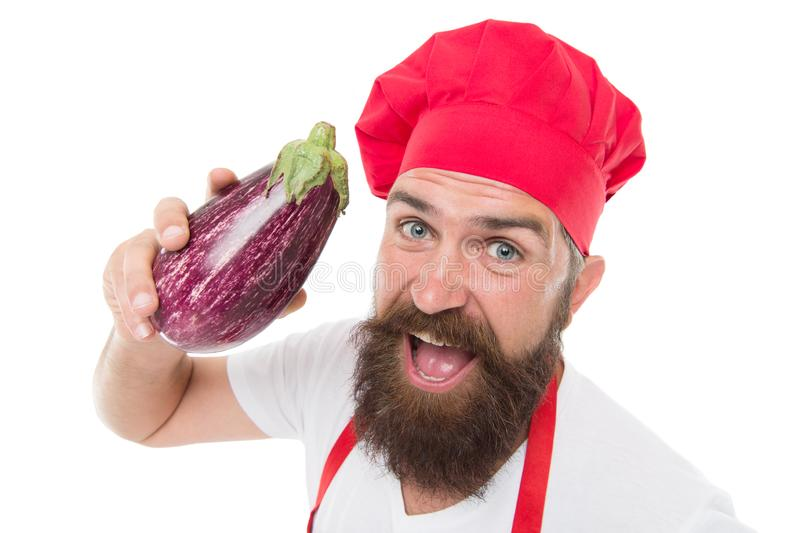 Vegetarian restaurant. Healthy cooking concept. Man with beard white background. Chef holds eggplant. Cook in uniform. Holds vegetables. Vegetarian recipe. Eat royalty free stock photography