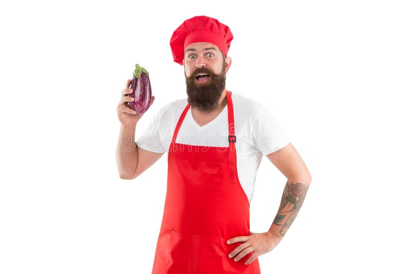 Vegetarian restaurant. Healthy cooking concept. Man with beard white background. Vegetarian recipe. Chef holds eggplant. Cook in uniform holds vegetables. Eat stock photo