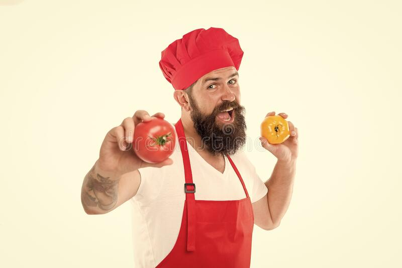 Vegetarian restaurant. Professional cook hold tomatoes in hands. Bearded man enjoy cooking vegetarian food. Vegetarian royalty free stock image