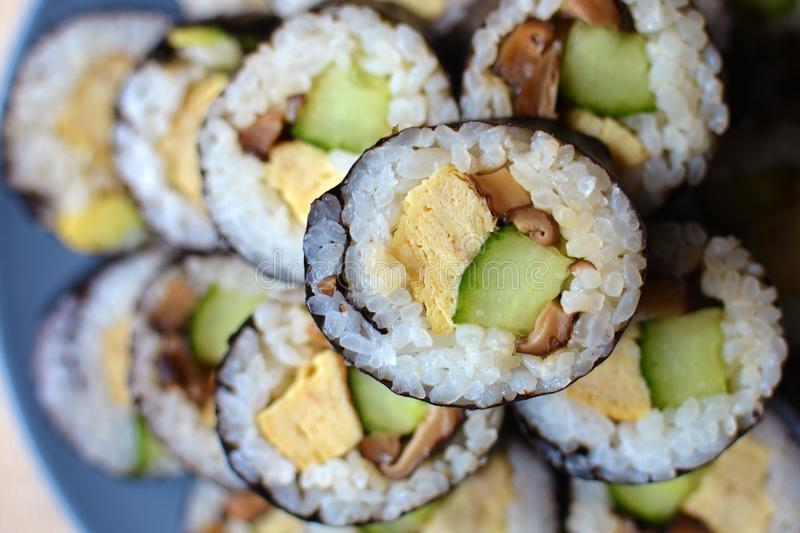 Vegetarian rolled sushi filled with egg, cucumber and asian shitake mushrooms stacked on a plate stock images
