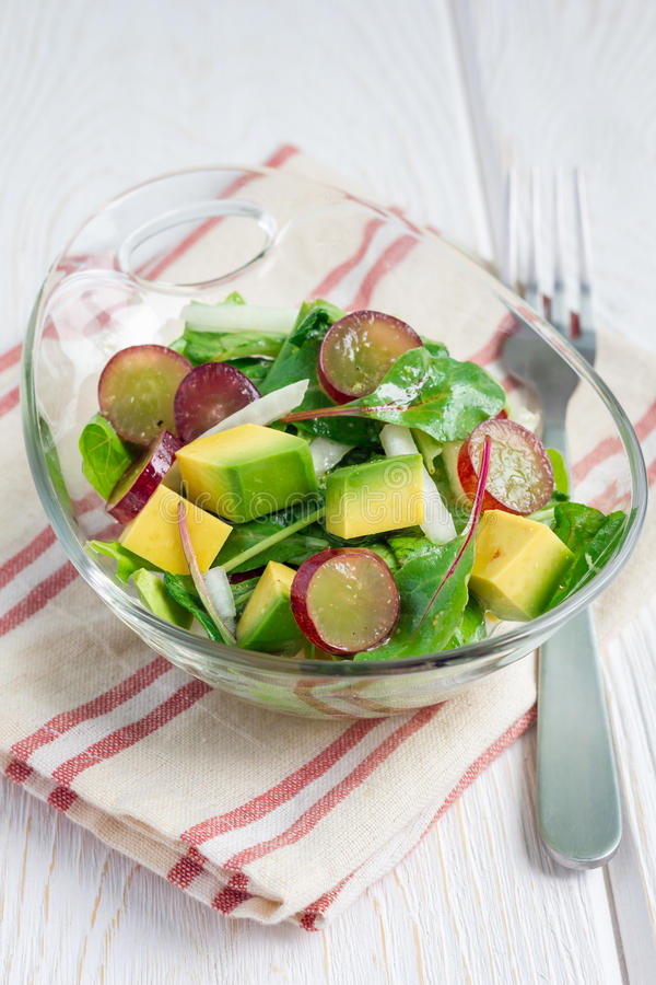 Vegetarian salad with avocado, grape, rucola, onion, in glass bowl royalty free stock image
