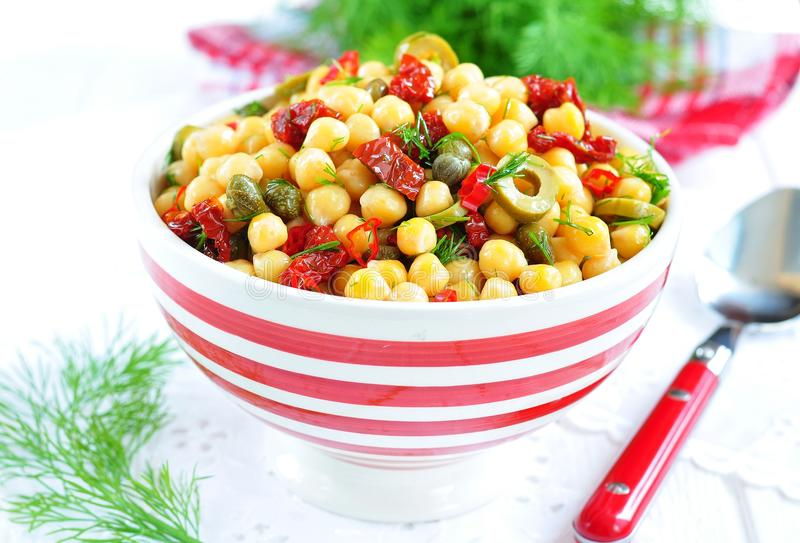 Vegetarian salad with chickpeas, dried tomatoes, capers and dill. Dinner stock photography