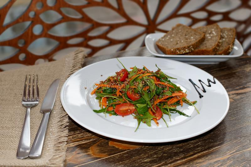 The vegetarian salad with vegetables, arugula and sprouted quinoa and unleavened bread. The vegetarian salad with vegetables, arugula and sprouted quinoa and stock photo
