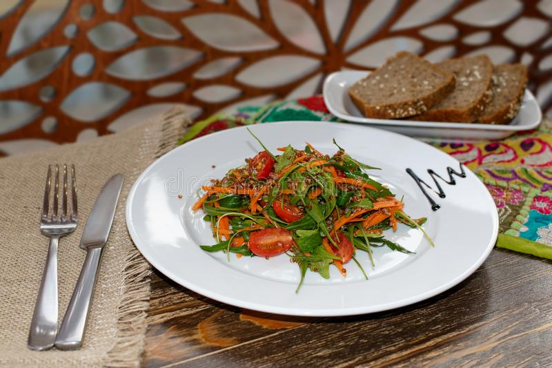 The vegetarian salad with vegetables, arugula and sprouted quinoa and unleavened bread on white plates. The vegetarian salad with vegetables, arugula and royalty free stock image