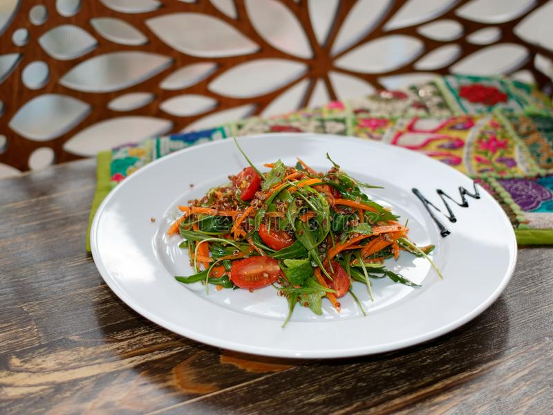 The vegetarian salad with vegetables, arugula and sprouted quinoa on white plate on wooden table. The vegetarian salad with vegetables, arugula and sprouted royalty free stock photos