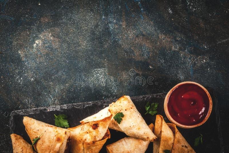 Vegetarian samsa samosas. Asian food. Vegetarian samsa samosas with tomato sauce. Dark blue background copy space top view stock image