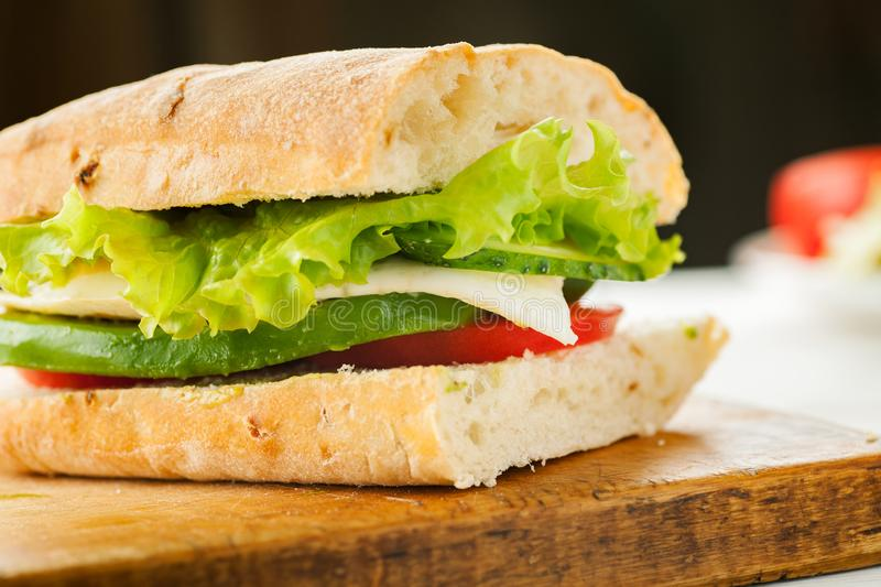 Vegetarian sandwich with avocado, tomato, egg and green salad on a wooden board royalty free stock photos