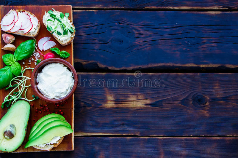 Vegetarian Sandwiches. Close up of Sandwiches with avocado, radish, sprouts, cream cheese, herbs and spices, wholegrain bun on rustic wooden board over dark royalty free stock images