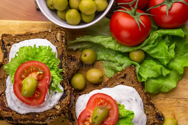 Vegetarian sandwiches with healthy rye bread, cheese cream, tomatoes, green olives and lettuce on table, top view. Healthy food stock photo