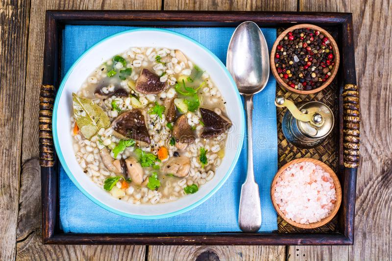 Vegetarian soup with mushrooms and pearl barley for lunch on wooden table royalty free stock image