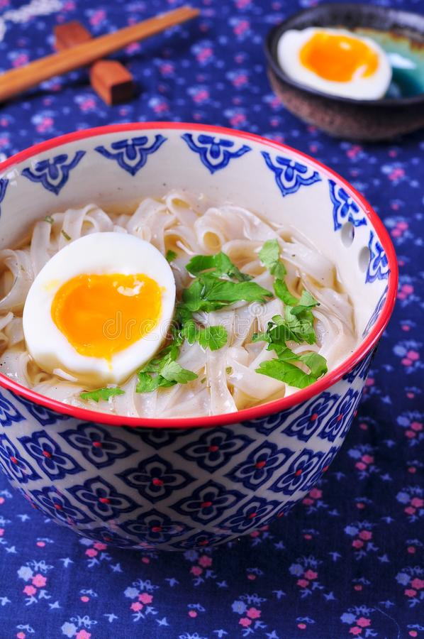 Vegetarian soup of rice noodles with parsley and boiled egg stock photos