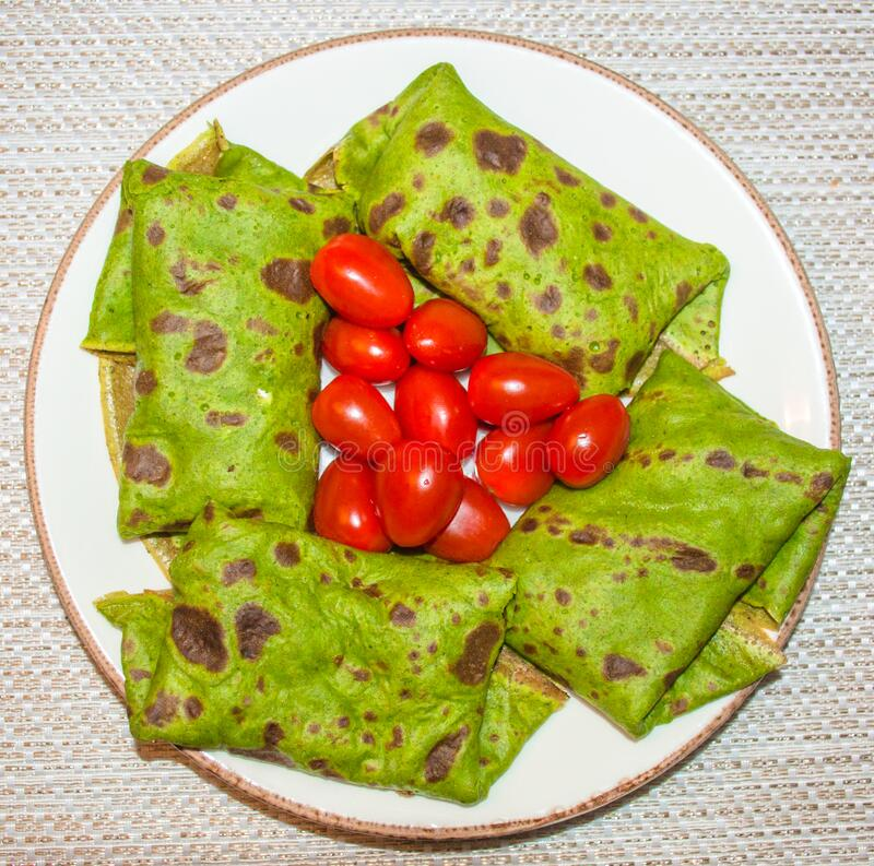 Vegetarian spinach green pancakes and small red tomatoes stock photo