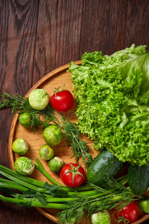 Vegetarian still life of fresh vegetables on wooden plate over rustic background, close-up, flat lay. stock images