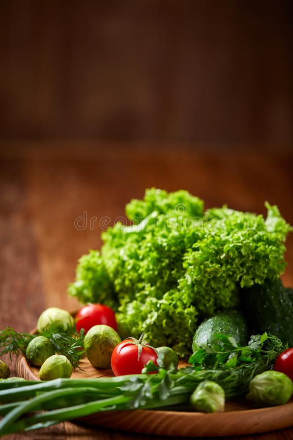 Vegetarian still life of fresh vegetables on wooden plate over rustic background, close-up, flat lay. royalty free stock photos