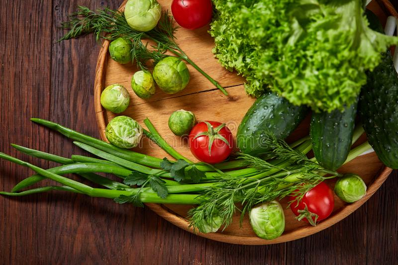 Vegetarian still life of fresh vegetables on wooden plate over rustic background, close-up, flat lay. stock image