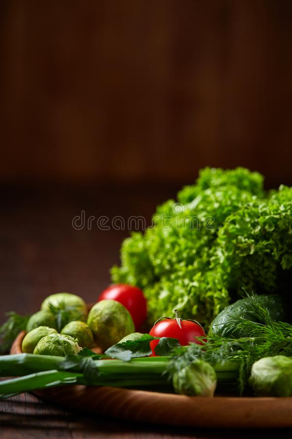 Vegetarian still life of fresh vegetables on wooden plate over rustic background, close-up, flat lay. royalty free stock photo