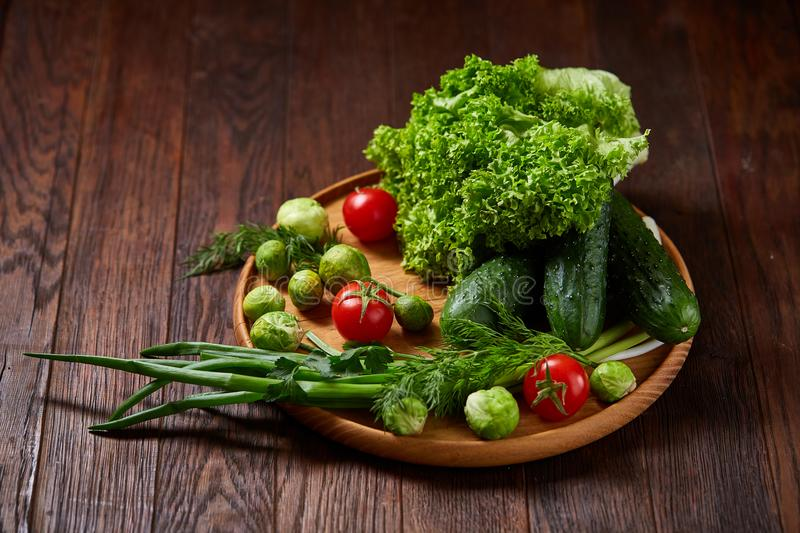 Vegetarian still life of fresh vegetables on wooden plate over rustic background, close-up, flat lay. royalty free stock image