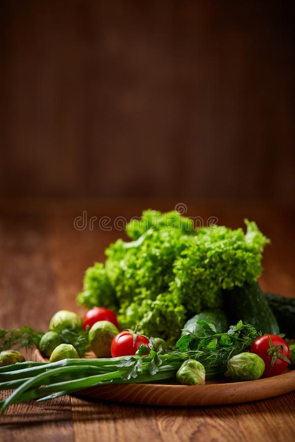 Vegetarian still life of fresh vegetables on wooden plate over rustic background, close-up, flat lay. stock photo