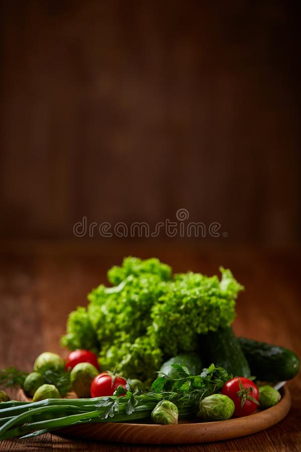Vegetarian still life of fresh vegetables on wooden plate over rustic background, close-up, flat lay. stock photography