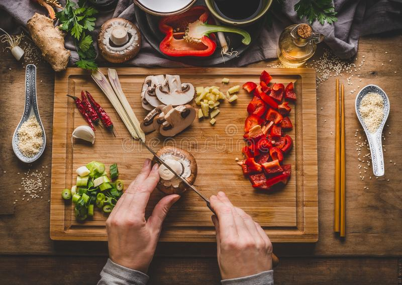 Vegetarian stir fry cooking preparation. Women female hands cut vegetables for stir fry on kitchen table background with ingredien. Ts, top view. Asian food royalty free stock image