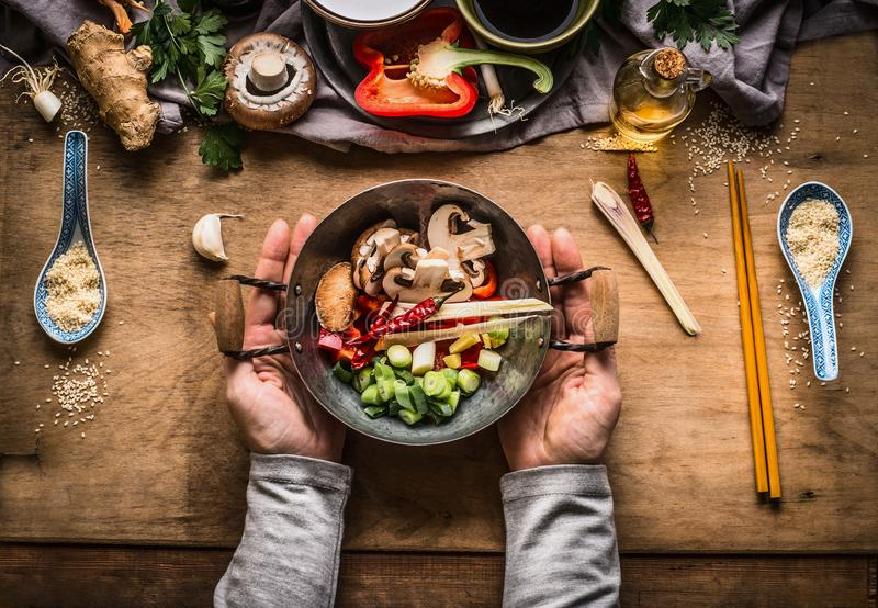 Vegetarian stir fry cooking preparation. Women female hands holding little wok pot with chopped vegetables for stir fry on kitchen royalty free stock images