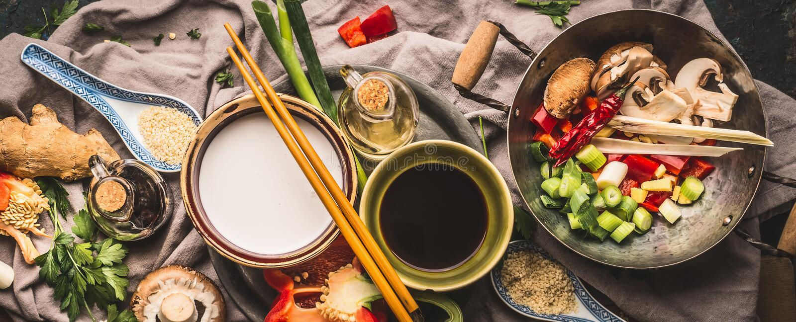 Vegetarian stir fry ingredients: chopped vegetables, spices, coconut milk, soy sauce, wok and chopsticks, top view, banner. Asian stock photo