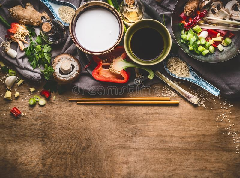 Vegetarian stir fry ingredients with coconut milk, soy sauce and chopsticks on wooden background, top view, border. Asian food royalty free stock photos