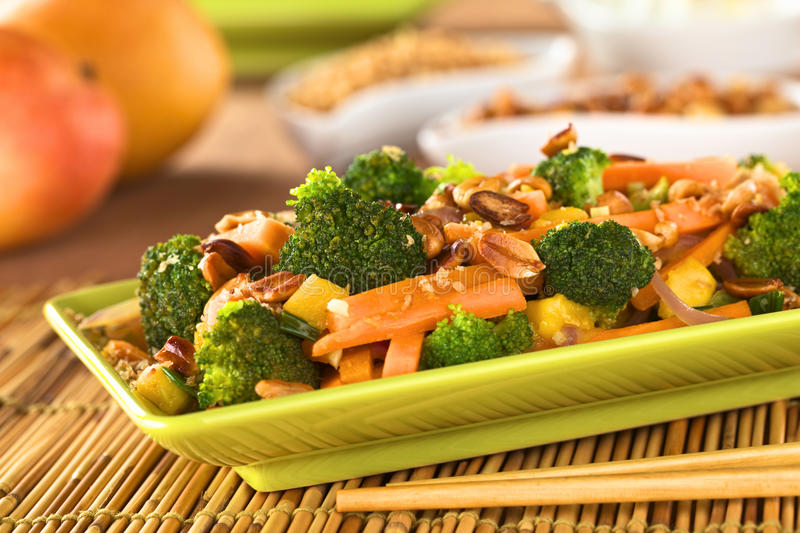 Vegetarian Stir-Fry Thai-Style. With broccoli, carrot, onion, mango with fried coconut flakes and peanuts (Selective Focus, Focus on the broccoli in the middle royalty free stock image