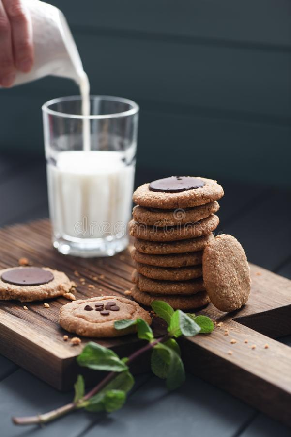 Vegetarian sweets for healthy sugar free breakfast. Peanut butter and almond cookies with chocolate drops served with plant milk stock photos