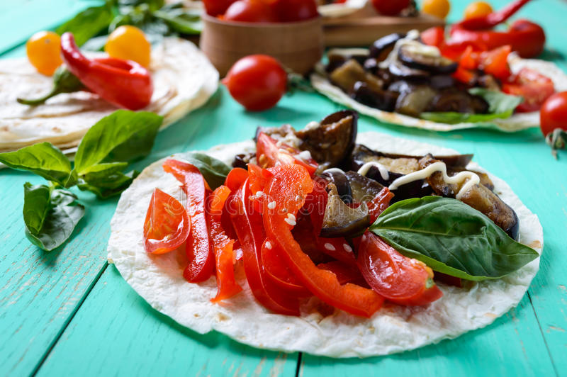 Vegetarian tacos with eggplant, cherry tomatoes, sweet peppers on a bright wooden background. royalty free stock images