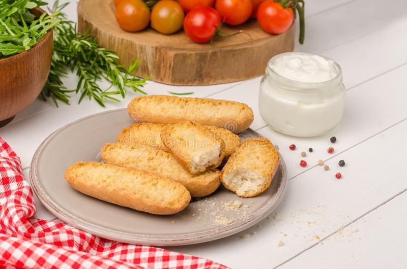 Vegetarian toasts with cream cheese, tomatoes, arugula, rosemary and black pepper on rustic wooden table stock image