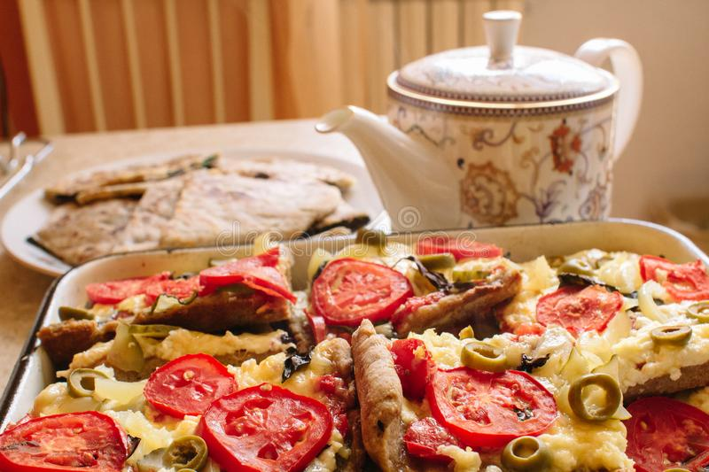 Vegetarian treats pizza with tomatoes, mozzarella and olives and naan with cheese and greens stock photo