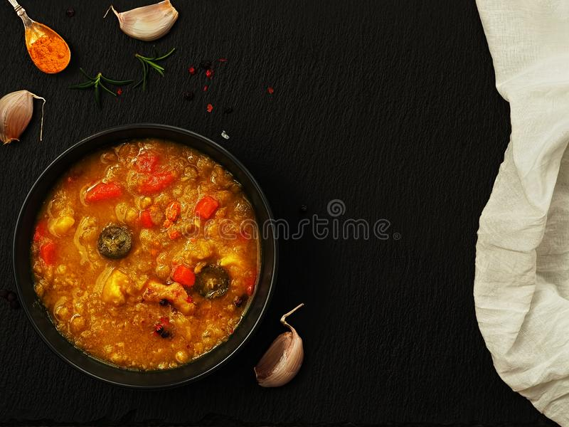 Vegetarian and vegan yellow pea soup with carrots, paprika and turmeric. Soup on a black stone background, next to cloves of royalty free stock photography