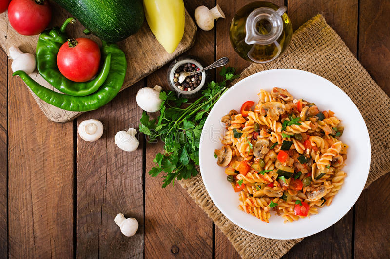 Vegetarian Vegetable pasta Fusilli with zucchini, mushrooms and capers in white bowl on wooden table. Top view stock photos