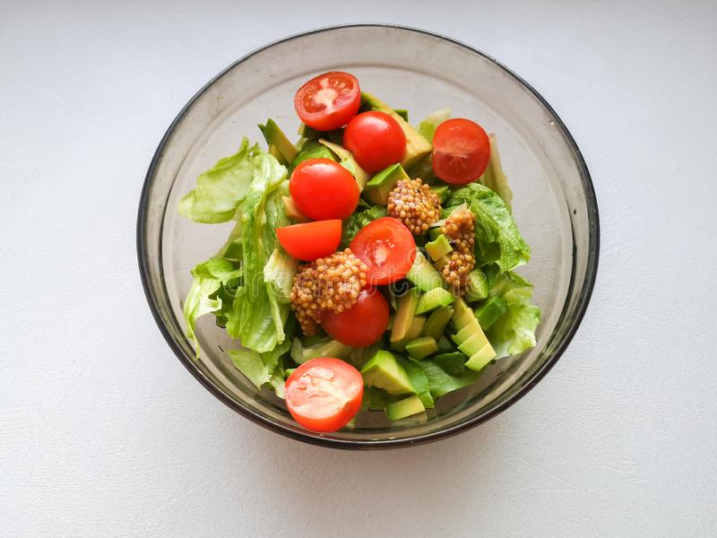 Vegetarian vegetable salad. Fresh salad flying to bowl in super slow motion. Avocado Tomato Salad stock image