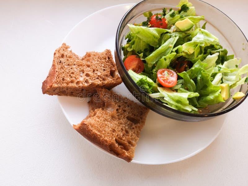 Vegetarian vegetable salad. Fresh salad flying to bowl in super slow motion. Avocado Tomato Salad stock photo