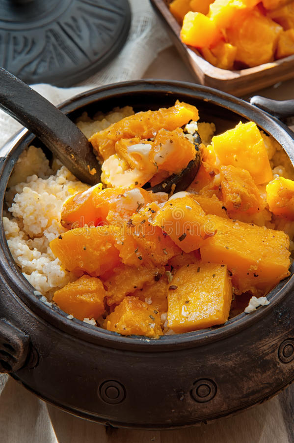 Vegetarian wheat porridge with large bright orange pieces of juicy fried pumpkin in a clay pot in a rustic style organic food royalty free stock photography