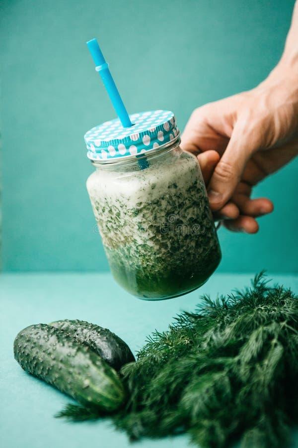 Vegetariangräsplanblandning av grönsak- och fruktcoctailen från gurkan och gräsplanpersilja och dill Personen tar en krus royaltyfri foto