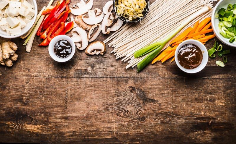 Vegetariano asiático que cozinha ingredientes para a fritada da agitação com tofu, macarronetes, gengibre, vegetais cortados, bro foto de stock