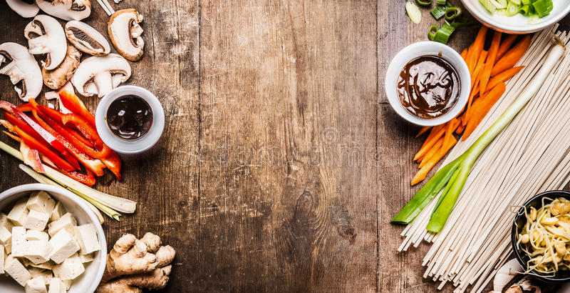 Vegetariano asiático que cozinha ingredientes para a fritada da agitação com tofu, macarronetes, vegetais e molhos no fundo rústi imagens de stock