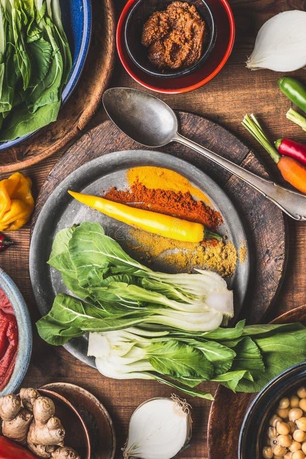 Vegetariano in buona salute che cucina gli ingredienti con le spezie a terra variopinte, ceci, pasta di curry indiana piccante, v immagine stock