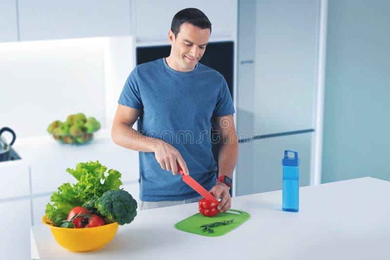Vegetariano de sorriso que está na cozinha e em cortar uma pimenta foto de stock