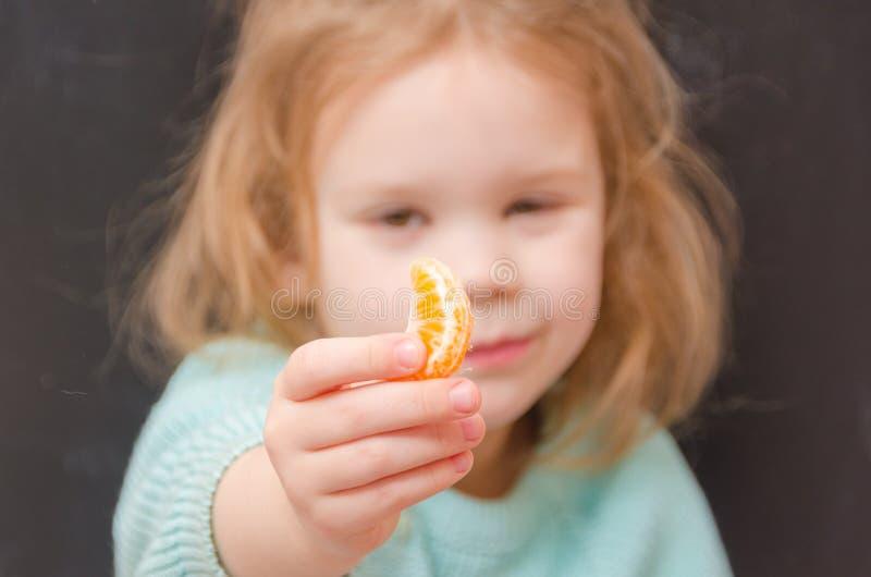 Vegetariano del bebé con la rebanada del mandarín imagenes de archivo