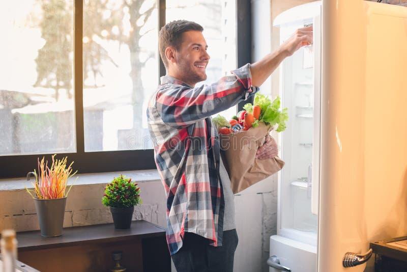Vegetariano do homem novo com os produtos de alimento biológico saudáveis fotografia de stock