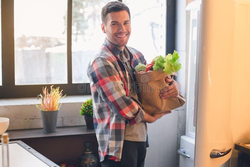 Vegetariano do homem novo com os produtos de alimento biológico saudáveis fotos de stock royalty free