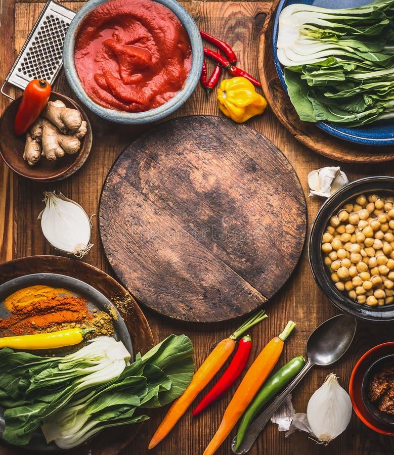 Vegetariano que cocina los ingredientes con el plato de los garbanzos, las especias coloridas, la goma de tomates, el jengibre y  imagen de archivo libre de regalías