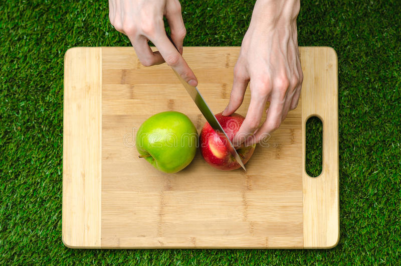 Vegetarians and cooking on the nature of the theme: human hand holding red and green apples on the background of a cutting board a. Nd green grass royalty free stock photos